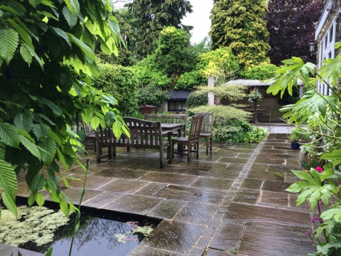 Mature garden outdoor dining area with pleached trees and york stone paving in Yorkshire