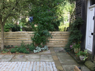 Garden landscaping fence and stone paving at Edwardian terrace garden by Paperbark Garden Design in Yorkshire