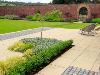 Large walled garden in Yorkshire with terrace of setts and stone paving also box hedges and herbaceous border