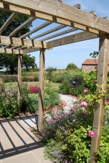 cottage garden landscape planting in Yorkshire by Paperbark garden design pergola and rose