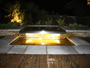 Lighting of a water feature on garden patio with Decking and Stone