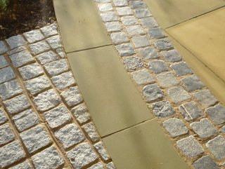 Stone setts with Yorkshire paving curve at landscaped garden by Paperbark Garden design