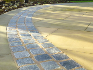 Stone setts circle with Yorkshire paving at landscaped garden by Paperbark Garden design