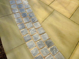 Stone setts with smooth Yorkshire paving at landscaped garden by Paperbark Garden design